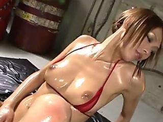 Oiled up babe in bikini gagging two throbbing cocks